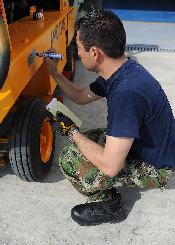A Colombian air force member labels a generator with the proper weight and balance before loading it onto an aircraft during an Air Mobility Command Building Partner Capacity mission at General Alberto Pauwels Rodriguez Air Base in Barranquilla, Colombia, June 27.  (U.S. Air Force photo by Tech. Sgt. Lesley Waters)