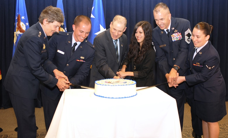 The Space and Missile Systems Center's youngest officer, civilian and enlisted airman are joined by Lt. Gen. Ellen Pawlikowski, SMC commander;  Douglas Loverro, SMC executive director; and Chief Master Sgt. Jonathan Rossetti, 61st Medical Squadron superintendent;  in cutting the ceremonial cake marking SMC's 58th birthday, June 27. (Photo by Sarah Corrice)