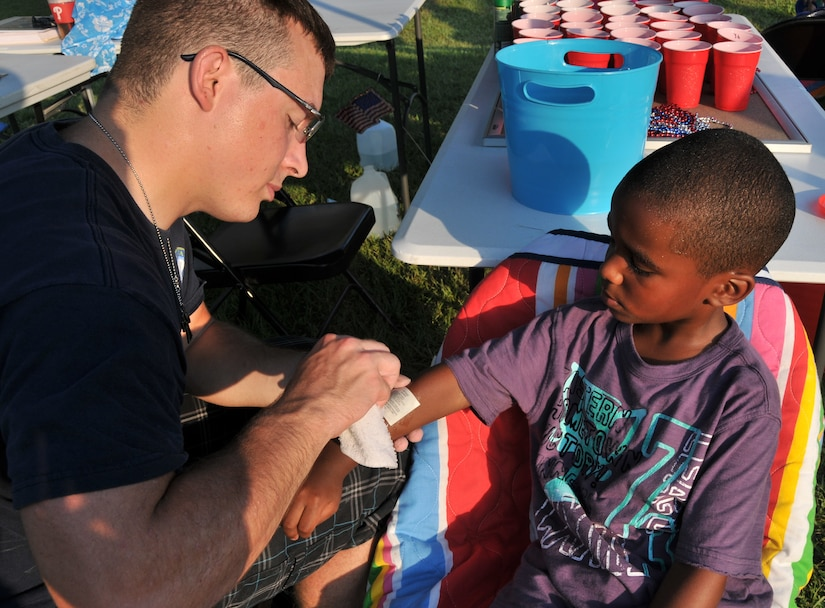 Petty Officer 3rd Class Levi Brazille, a graduate from Navy Nuclear Power Training Command, places a temporary tattoo on Elijah Walls June 29, during the 2012 Freedom Fest at Marrington Plantation at Joint Base Charleston – Weapons Station. Walls is the son of Master Sgt. Jadirra Walls, 437th Maintenance Squadron first sergeant and Tech. Sgt. Darnell Walls from the 628th Civil Engineer Squadron fire department. Nearly 1,500 Sailors, Airmen, civilians and their families attended the fest which included food, drinks, festival rides, music and fireworks. (U.S. Air Force photo/Airman 1st Class Jared Trimarchi)