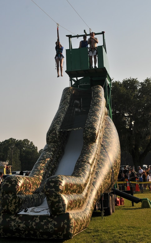 Master Sgt. Jason Miller, 373rd Training Squadron Command Support Staff non-commissioned officer in charge and his daughter, Ana, descend a zip-line June 29, during the 2012 Freedom Fest at Marrington Plantation at Joint Base Charleston – Weapons Station. Nearly 1,500 Sailors, Airmen, civilians and their families attended the fest which included food, drinks, festival rides, music and fireworks. (U.S. Air Force photo/Airman 1st Class Jared Trimarchi)