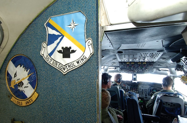 Oversized emblems attached to a wall of an E-3 Sentry jet lead to the cramped cockpit where five members navigate and fly the AWACS during a June 11 training mission. High over the bright clouds of a developing Missouri thunderstorm, the crew works through checklists and reacts to emergency training, keeping themselves ready for the real-world call. (Air Force photo by Margo Wright)
