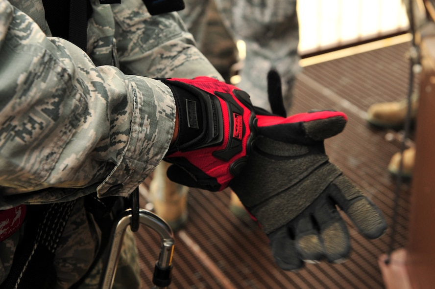 SPANGDAHLEM AIR BASE, Germany – Airman 1st Class Cory Gonzales, 52nd Civil Engineer Squadron firefighter, puts on gloves before rappel training at the control tower here June 29. Firefighters from the 52nd CES complete rappelling training so they can be rescue certified to perform rope and high-angle rescue techniques. The firefighters train annually to ensure the force maintains the highest level of proficiency and readiness for rapid rescue attempts in demanding situations. (U.S. Air Force photo by Airman 1st Class Dillon Davis/Released)