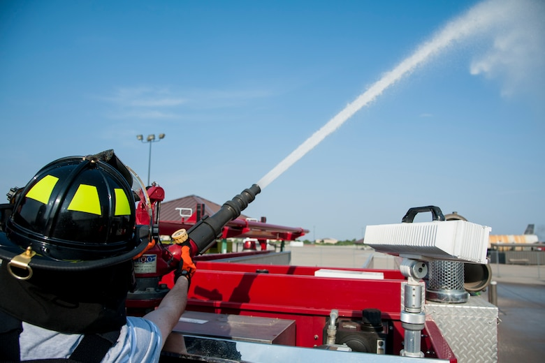 """GOODFELLOW AIR FORCE BASE, Texas-- Maxwell """"Trey"""" Pons III, Honorary Air Force firefighter, sprays a turret on top of a fire truck at the Louis F. Garland DOD Fire Academy June 28. Pons, who is autistic, sight impaired and hearing-impaired, accomplished his dream to become a firefighter by going through each training block in a day at the Fire Academy. (U.S. Air Force photo/Airman 1st Class Michael Smith)"""