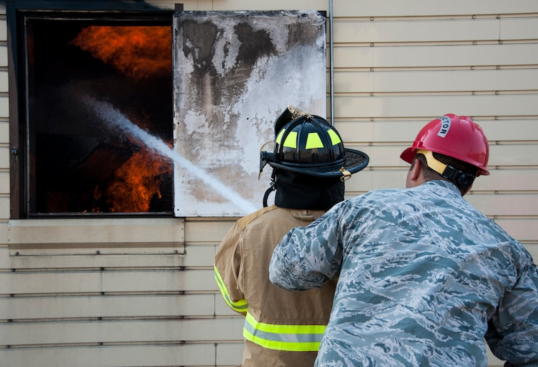 """GOODFELLOW AIR FORCE BASE, Texas-- Maxwell """"Trey"""" Pons III, Honorary Air Force firefighter, extinguishes a simulated interior fire with the help of Staff Sgt. Michael Barbett, 312th Training Squadron instructor, at the Louis F. Garland DOD Fire Academy June 28. Pons, who is autistic, sight impaired and hearing-impaired, accomplished his dream to become a firefighter by going through each training block in a day at the Fire Academy. (U.S. Air Force photo/Airman 1st Class Michael Smith)"""