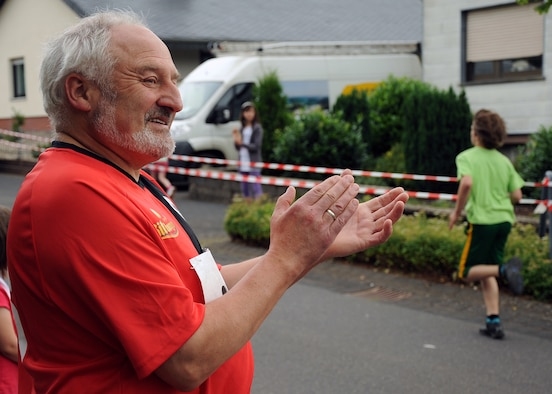 SPANGDAHLEM AIR BASE, Germany – Arnold Weber, German-American Friendship Run participant, claps as a child from the 13-16 year old age group approaches the finish line of a 1,700 meter race in Binsfeld July 1. The race organizers separated the runs into six categories to balance ability levels. More than 300 Germans and Americans participated in the ninth annual run, which focuses on building partnerships and relationships between the two countries' peoples. (U.S. Air Force photo by Staff Sgt. Daryl Knee/Released)