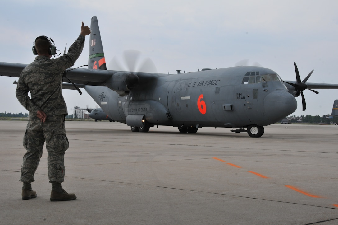 Airman 1st Class Tucker Smith, 153rd Maintenance Squadron crew chief, marshals a MAFFS-equipped C-130 assigned to the 146th Airlift Wing, Channel Islands, Calif., July 3, 2012, at the Wyoming Air National Guard base. MAFFS aircraft continue to operate in the Rocky Mountain region to assist with firefighting efforts. (U.S. Air Force photo by 1st Lt. Rusty Ridley)