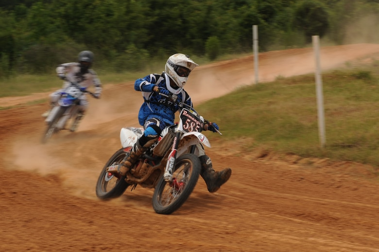 Airman 1st Class Michael Romanyak, 2nd Maintenance Squadron, speeds through a turn at a dirt track in Mansfield, La., July 1. Romanyak has been riding dirt bikes since he was 12 years old and enjoys competing in local Motocross competitions. (U.S. Air Force photo/Airman 1st Class Micaiah Anthony)(RELEASED)