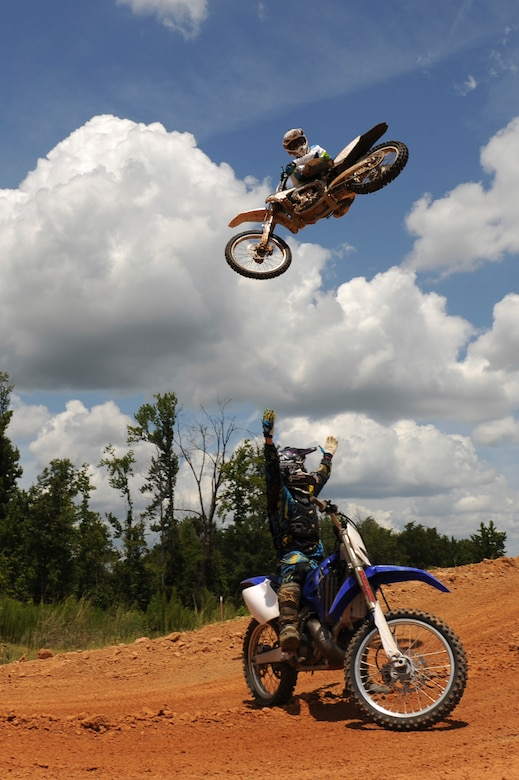 A local dirt bike enthusiast jumps over a fellow rider at a dirt track in Mansfield, La., July 1. A few Barksdale Air Force Base Airmen enjoy riding and racing dirt bikes to unwind after a long work week. In order to ride and race dirt bikes, Airmen must complete the motorcycle safety course at Barksdale Air Force Base along with having a high-risk activity briefing from their commander. (U.S. Air Force photo/Airman 1st Class Micaiah Anthony)(RELEASED)