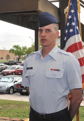 Airman Luke Bolen, who recovered from Guillain-Barre Syndrome, stands in front of the U.S. flag during the Air Force Basic Military Training graduation ceremony May 11 at the 321st Training Squadron. (U.S. Air Force photo/Alan Boedeker)
