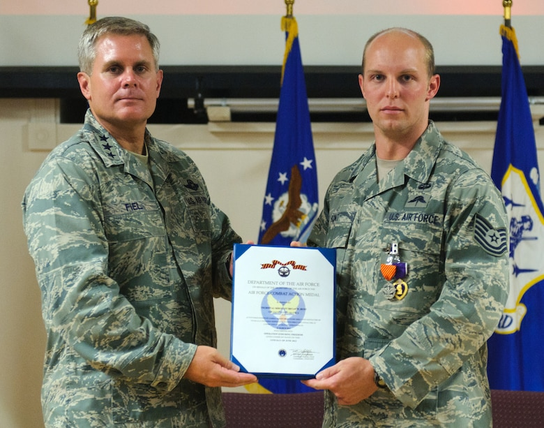 Lt. Gen. Eric Fiel, commander of the U.S. Air Force Special Operations Command, presents an Air Force Combat Action Medal to Tech. Sgt. Bryan Hunt, 123rd Special Tactics Squadron combat controller, at the Kentucky Air National Guard Base in Louisville, Ky., on June 28, 2012. Hunt was also awarded a Purple Heart for being wounded in action while serving overseas. (U.S. Air Force photo by Master Sgt. Phil Speck)