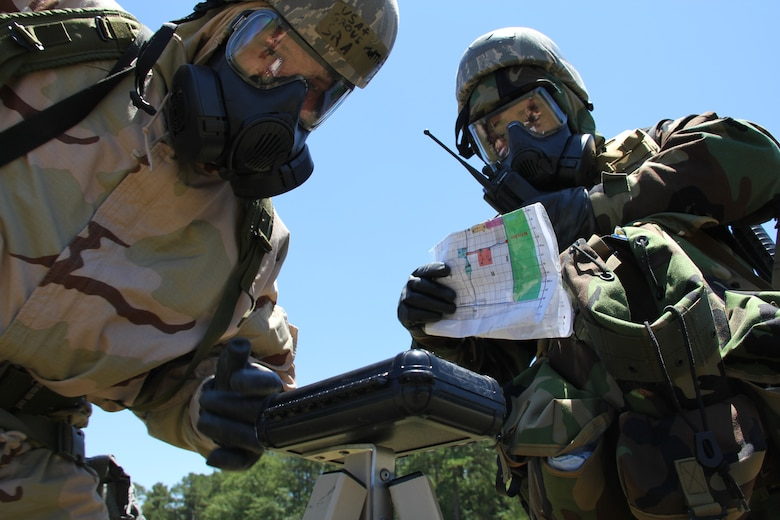 ROBINS AIR FORCE BASE, Ga. -- Senior Airman Matthew Grove, 52nd Combat Communications Squadron radio frequency transmissions technician, reviews chemical agent sensitive paper placed on a stanchion while Staff Sgt. Brandon Cook, 52nd Communications Squadron radio frequency transmission technician, calls in a status of their findings on a land mobile radio during the Warrior Air Base training area here June 25-27. More than 70 members of the unit participated in ATSO training in preparation for the unit's upcoming operational readiness inspection. The three-day exercise included classroom and field training with a concentration on self-aid and buddy care, chemical warfare and law of armed conflict. (U.S. Air Force photo by Robert Talenti)