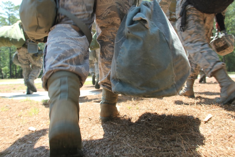 ROBINS AIR FORCE BASE, Ga. -- Members of the 52nd Combat Communications Squadron carry helmets, bags and chemical warfare gear to their simulated deployed location during the ability to operate and survive (ATSO) exercise at the Warrior Air Base training area here June 25-27. More than 70 members of the unit participated in ATSO training in preparation for the unit's upcoming operational readiness inspection. The three-day exercise included classroom and field training with a concentration on self-aid and buddy care, chemical warfare and law of armed conflict. (U.S. Air Force photo by Robert Talenti)