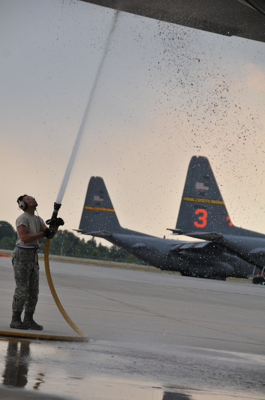 Staff Sgt. Efren Enriquez, 30th Airlift Squadron propulsion craftsman, sprays the tail of a MAFFS-equipped C-130 on the flightline in Cheyenne, Wyo., July 3, 2012. MAFFS aircraft continue to operate in the Rocky Mountain region to assist with firefighting efforts. (U.S. Air Force photo by 1st Lt. Rusty Ridley)