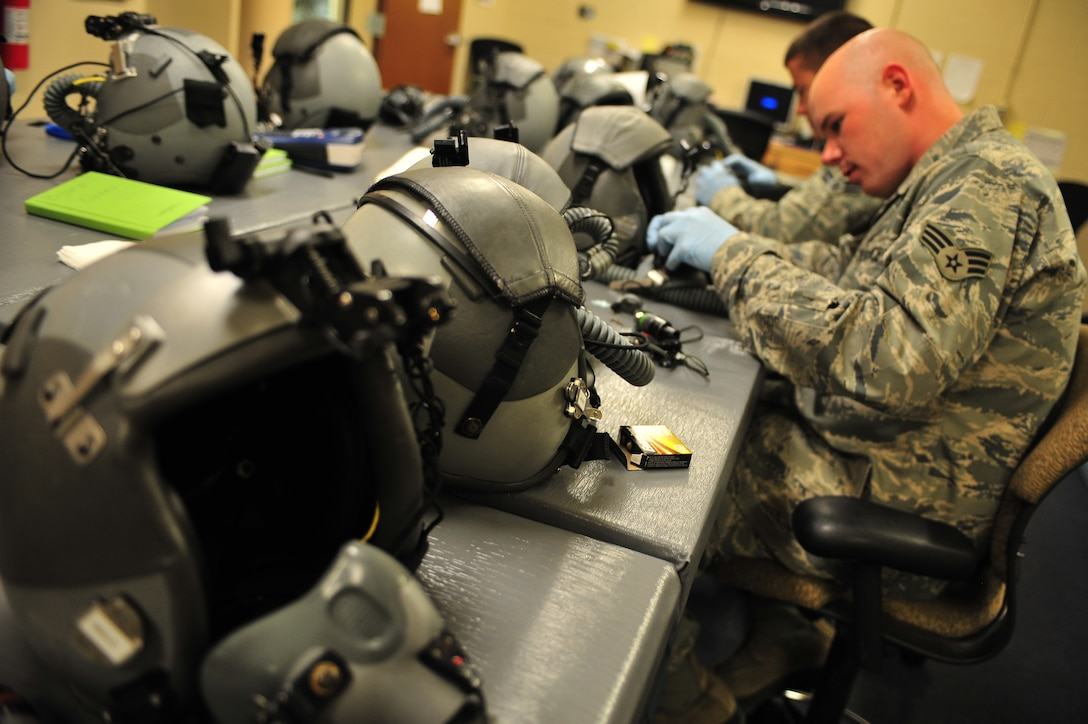 U.S. Air Force Senior Airman Nicholas Byars and Airman 1st Class Robert McClung, 27th Special Operations Support Squadron aircrew flight equipment specialists, inspect and adjust components on helmets and oxygen masks at Cannon Air Force Base, N.M., July 3, 2012. Aircrew flight equipment specialists inspect, maintain and adjust life support and survival gear for flight crew members assigned to Cannon. (U.S. Air Force photo by Airman 1st Class Eboni Reece)