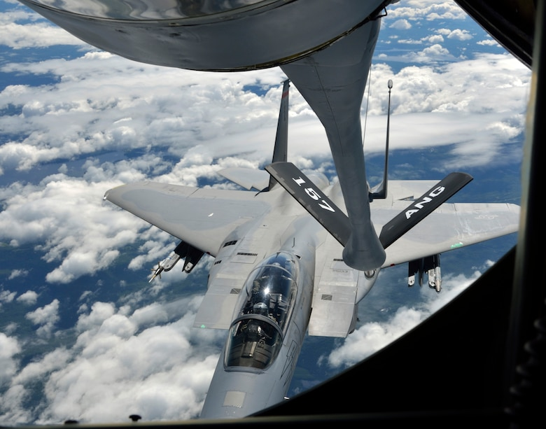 """The 157th Air Refueling Wing, Pease NH, prepares to refuel an F-15 from the 104th Fighter Wing, Westfield MA, high above northern New England on June 29, 2012. In Prone position, boom operator TSgt. Justin Poteet of the 157th will transfer fuel that will allow the F-15s to continue their """"dog fight"""" training exercises. (U.S. Air Force photo/SrA. Kelly Galloway)"""