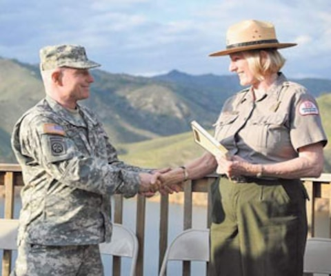 VISALIA, CALIF., -- Army Corps of Engineers Maj. Gen. Bo Temple hands Valerie McKay, a park ranger with the corps, a book on Thursday at Lake Kaweah. Temple flew from Washington, D.C., in part, to meet McKay, whose late grandfather fought in World War I for the British and participated in the 1914 Christmas Day Truce.