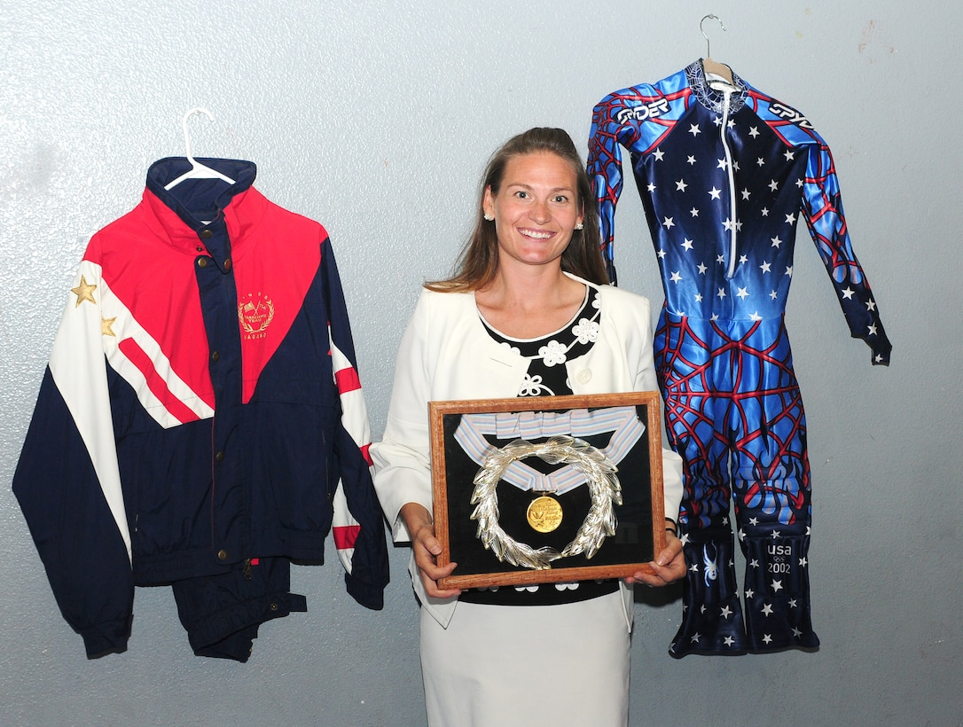 Jennifer Kelchner, a Paralympics gold medalist poses for a photo with her gold medal and her Olympic uniforms at the Youth Center at Beale Air Force Base, Calif., June 27, 2012. Kelchner also won the bronze medal for the slalom skiing event at the 2002 Winter Olympics in Salt Lake City, Utah. (U.S. Air Force photo by Senior Airman Allen Pollard)
