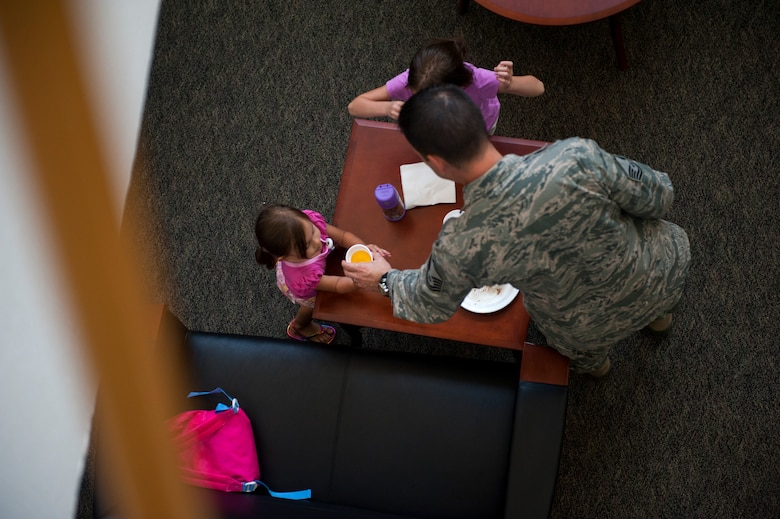 Master Sgt. Shane Chandler, Air Force Special Operations Command logistics office, serves his daughters, Cara, 2, and Leighlin, 5, drinks during AFSOC's Bring your Child to Work Day, June 29, 2012, at Hurlburt Field, Fla. (U.S. Air Force photo by Staff Sgt. David Salanitri)