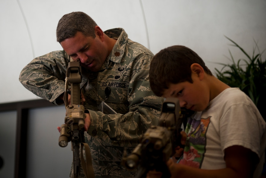 Maj. Bradley Ball, Air Force Special Operations Command Staff Judge Advocate, and son Garrette, 11, look through the optics of weapons commonly used by AFSOC Airmen, June 29, 2012, during AFSOC's Bring Your Child to Work Day at Hurlburt Field, Fla. (U.S. Air Force photo by Staff Sgt. David Salanitri)