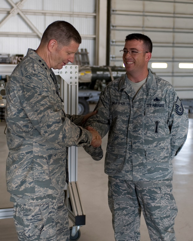 U.S. Air Force Lt. Gen. Robin Rand, 12th Air Force commander, left, presents Master Sgt. Troy Drasher, 7th Munitions Squadron weapons standardization crew member, with a commander's coin during his tour of the load crew training facility July 2, 2012, at Dyess Air Force Base, Texas. During his visit, Rand