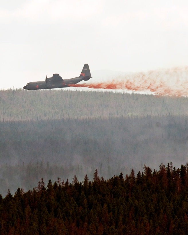 A C130-J equipped with Modular Airborne Firefighting Systems (MAFFS) from the 146th Airlift Wing in Port Hueneme, Calif. drops retardant near the Squirrel Creek fire about 70 miles east of Cheyenne. MAFFS is a self-contained aerial firefighting system owned by the U.S. Forest Service that can discharge 3,000 gallons of water or fire retardant in less than 5 seconds, covering an area one-quarter of a mile long by 100 feet wide. Once the load is discharged, it can be refilled in less than 12 minutes. (U.S. Air Force photo / Senior Airman Nicholas Carzis)