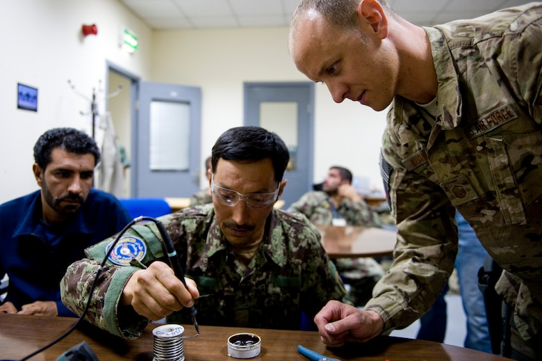 U.S. Air Force Master Sgt. Jamie Kuranda, a C-27A maintenance advisor with the 440th Air Expeditionary Advisory Squadron, wathes an Afghan air force electronic and avionics student solder a piece of wire, in Kabul, Afghanistan on July 7, 2012. The mission of the 440th AEAS is to train, mentor and advise Afghan air force Kabul Air Wing members capable of sustaining a healthy fleet that is ready to perform training and operational missions in support of Afghan national security requirements today and in the future. (U.S. Air Force photo by Staff Sgt. Greg C. Biondo)(Released)