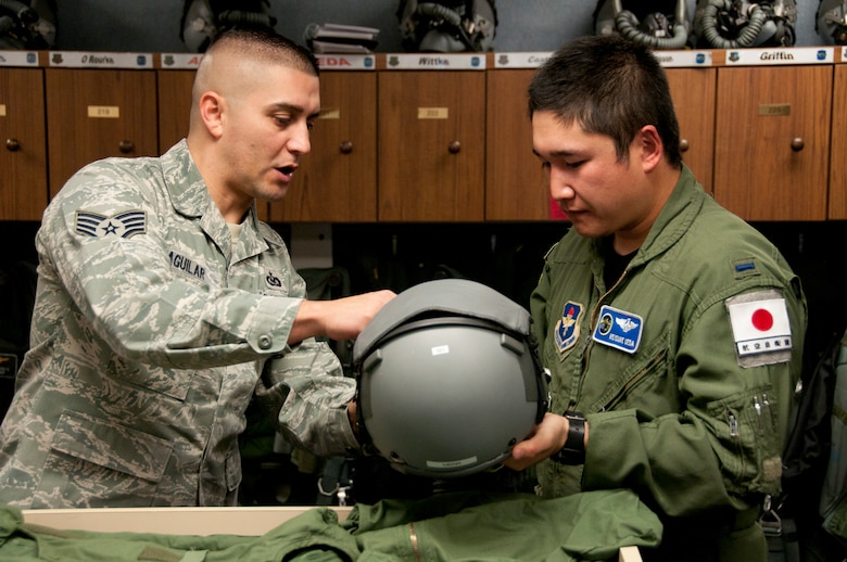Japan Air Self-Defense Force 1st Lt. Keisuke Ueda pre-flights his helmet with the help of Staff Sgt. Luis Aguilar, an aircrew flight equipment specialist at the 162nd Fighter Wing at Tucson International Airport, Feb. 22. Ueda is one of three Japanese students currently enrolled in F-16 initial pilot training here. (U.S. Air Force photo/Master Sgt. Dave Neve)