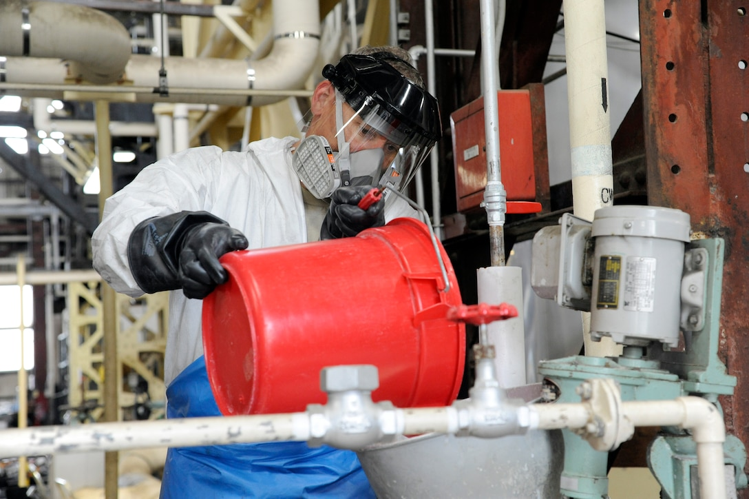 U.S. Air Force Chief Master Sgt. James Laurent, 35th Fighter Wing command chief, pours chemicals into the supply side of the boilers at the main boiler plant on Misawa Air Base, Japan, July 10, 2012. Without maintenance, the boiler becomes unusable after two years. However, when cleaned annually, the boiler will last for 20 years. (U.S. Air Force photo by Tech. Sgt. Marie Brown)