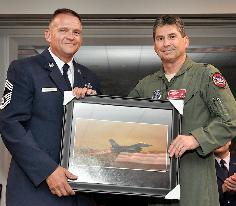 Brigadier General Michael Hepner presented an F-16 photograph to Chief Master Sergeant Randy Bachmann, Detachment 1, Chief Enlisted Manager, in honor of his 26 year Air Force career at a retirement ceremony held 28 June 2012, at Ellington Field, Houston Texas.  CMSgt Bachmann served 20 of his 26 years at alert detachments.