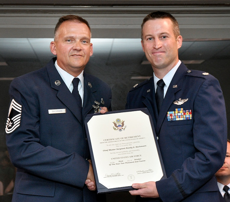 Lt Col Craig Borgstrom presents a certificate of retirement to Chief Master Sergeant Randy Bachmann, Detachment 1, Chief Enlisted Manager, in honor of his 26 year Air Force career at a retirement ceremony held 28 June 2012, at Ellington Field, Houston Texas.  CMSgt Bachmann served 20 of his 26 years at alert detachments.