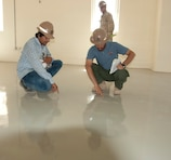 AFGHANISTAN — Eraj Akbarpoor, Afghan quality assurance representative, (left) and Tariq Taheri, Afghan project engineer, inspect a floor in one of several buildings nearing completion on the 9th Commando compound in Herat, July 2, 2012.