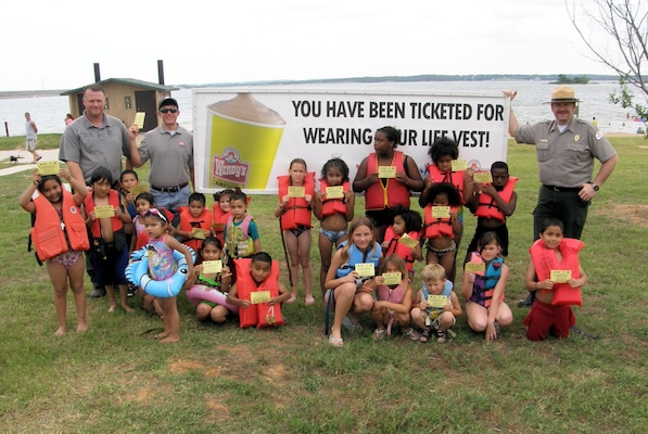 "DENISON, Texas — Tommy Holder (left), and Josh Wingfield, both Park Rangers with the U.S. Army Corps of Engineers Tulsa District, along with Student Conservation Association intern Matt Mueller pose with a group of children who have learned about water safety at Lake Texoma. The Tulsa District has teamed with Wendy's to ""ticket"" children ""caught"" wearing life jackets. Each ticket is good for a free Frosty."