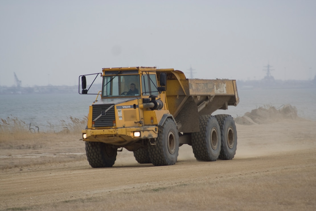Large dump trucks move material around the Norfolk District's Craney Island Dredged Material Management Area. The area is a 2,500-acre confined dredged material disposal site located near Norfolk, VA. Plans for the site were developed in the early 1940s to provide a long-term disposal area for material dredged from the channels and ports in the Hampton Roads area.