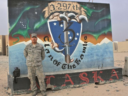 SOUTHEAST ASIA -- Alaska Air National Guardsman Senior Airman Cameron Mixsooke of Kenai, Alaska, stands in front of an Alaska National Guard mural during a recent deployument to Kuwait. Photo courtesy of Alaska Air Natinolal Guard.
