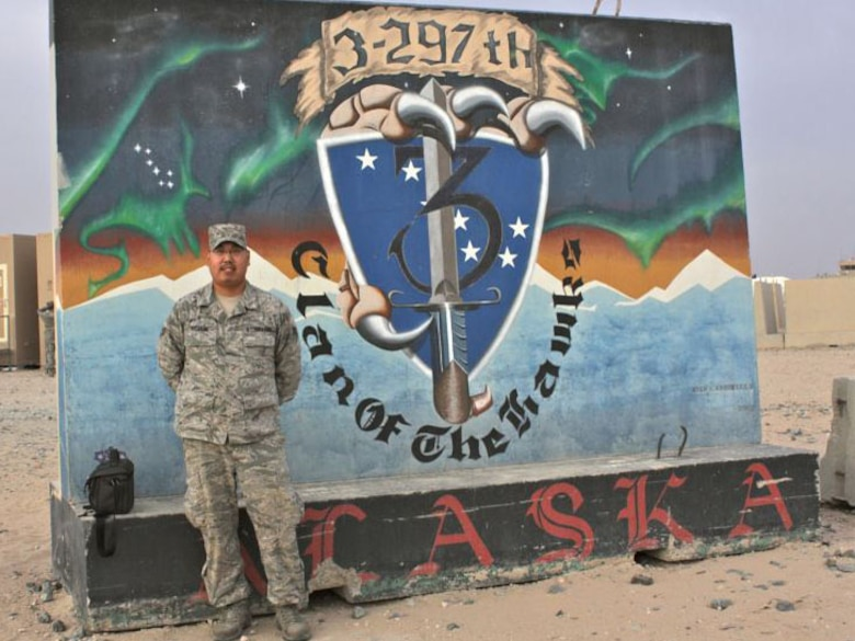 SOUTHEAST ASIA -- Alaska Air National Guardsman Senior Airman Cameron Mixsooke of Kenai, Alaska, stands in front of an Alaska National Guard mural during a recent deployument to Kuwait. Photo courtesy of Alaska Air Natinolal Guard.