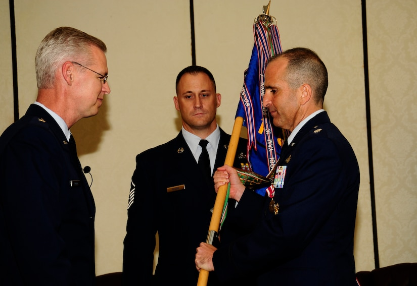 U.S. Air Force Lt. Col. Aaron Burgstien relinquishes command of the 1st Combat Camera Squadron to U.S. Air Force Brig. Gen. Les Kodlick, Office of the Secretary of the Air Force Director of Public Affairs, during a change of command ceremony at Joint Base Charleston, S.C., July 10. (U.S. Air Force Photo by Senior Airman Alexandra Hoachlander/ Released)