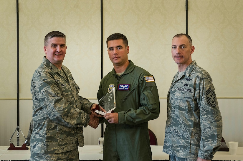 Col. Al Miller, 437th Airlift Wing vice commander, presents a Diamond Sharp award to Airman 1st Class Michael Graves, 15th Airlift Squadron loadmaster, along with Chief Master Sgt. Larry Williams, 437th AW command chief, at Joint Base Charleston - Air Base, S.C., July 10, 2012. Diamond Sharp awards are designed to recognize individuals in a unit who stand out to their first sergeant. (U.S. Air Force photo by Airman 1st Class George Goslin/Released)