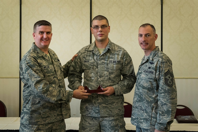 Col. Al Miller, 437th Airlift Wing vice commander, presents a Diamond Sharp award to Airman 1st Class Ryan Swapp, 437th Aircraft Maintenance Squadron aircraft flight instruments and navigation systems apprentice, along with Chief Master Sgt. Larry Williams, 437th AW command chief, at Joint Base Charleston - Air Base, S.C., July 10, 2012. Diamond Sharp awards are designed to recognize individuals in a unit who stand out to their first sergeant. (U.S. Air Force photo by Airman 1st Class George Goslin/Released)