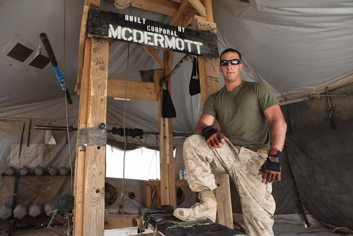 Corporal Frank McDermott, poses for a photo, July 7, 2012, by some of the gym equipment he built during his downtime in Afghanistan. Mcdermott, of Deleran, N.J., used his hobby of building things to help his hobby of working out.