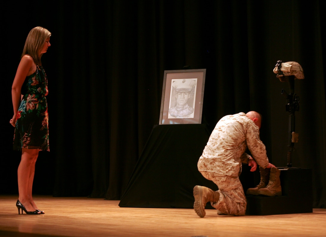 Marines, family and friends gathered at the base theatre June 29, at a memorial service to commemorate the life of Lance Cpl. Osbrany Montes De Oca. After the service Marines, friends and family members were given the opportunity to go up and pay their final respects to Lance Cpl. De Oca. (Official U.S. Marine Corps photo by Sgt. Bobby J. Yarbrough)