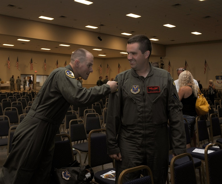 1st Lt. Paul Gabor, 11th Bomb Squadron Formal Training Unit, punches a unit patch on the flight suit of Capt. Seth Shipley, 96th Bomb Squadron, after graduating from his FTU class on Barksdale Air Force Base, La., July 10. FTU is a nine month course for pilots, navigators and electronic warfare officers out of their initial flight training. The course consists of academic studies, simulators and flight training where the students gain the experience and confidence to operate a B-52H Stratofortress. (U.S. Air Force photo/Airman 1st Class Benjamin Gonsier)(RELEASED)