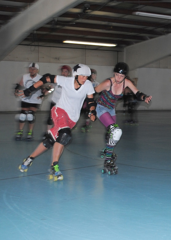 Capt. Cindy Tope, 40th Helicopter Squadron UH-1N pilot, left, tries to lap other Electric City Roller GrrrlZ members as she plays the role of a jammer during a practice at Hauers Family Skating Center on June 24. The team focuses on the basics of skating, fitness, drills and practice scrimmages in preparation for each bout. (U.S. Air Force photo/Airman 1st Class Katrina Heikkinen)