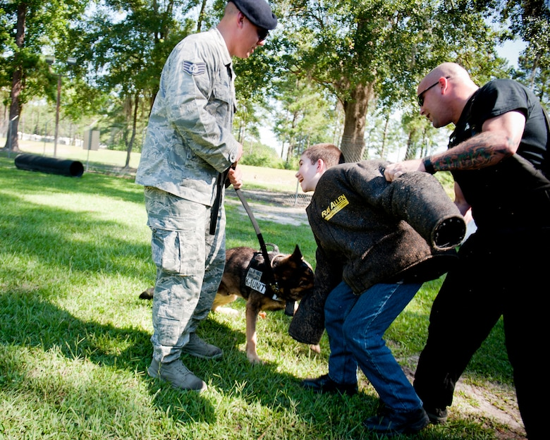 Christopher Carswell absorbs a bite from a military working dog with help from U.S. Air Force Staff Sgt. Andrew Fischer, left, and Tech. Sgt. David Smith, 23d Security Forces Squadron MWD handlers, at Moody Air Force Base, Ga., July 10, 2012. Christopher said the best part of the day with the canine unit was watching and participating in the dog bite demonstrations. (U.S. Air Force photo by Staff Sgt. Jamal D. Sutter/Released)