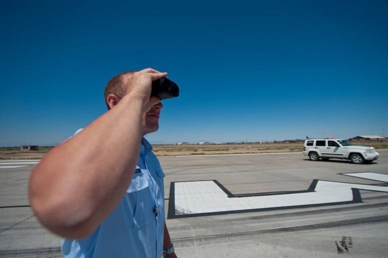 Senior Airman Christopher Proctor, 49th Operations Support Squadron airfield manager, uses a range finder to estimate the distance of objects on the airfield at Holloman Air Force Base, N.M., June 25. Airfield managers must know the exact whereabouts of all incoming and outgoing aircraft on the airfield. (U.S. Air Force photo by Airman 1st Class Daniel E. Liddicoet/Released)
