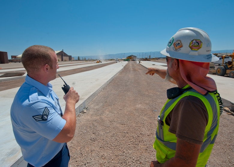 Senior Airman Christopher Proctor, 49th Operations Support Squadron airfield manager, and John Nappier, construction foreman, discuss on-going construction taking place on the airfield at Holloman Air Force Base, N.M., June 25. Airfield management is responsible for overseeing all construction projects taking place on the airfield and ensuring the safety and timeliness of all workers involved. (U.S. Air Force photo by Airman 1st Class Daniel E. Liddicoet/Released)