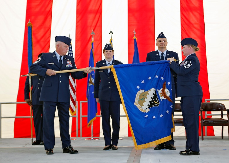 Chief Master Sgt. Christopher McCollor, Air Force Test Center command chief, ceremoniously rolls up the Air Force Flight Test Center flag, with the assistance of Master Sgt. Stephanie Brown, during a re-designation ceremony in Hangar 1600 July 13. Gen. Janet Wolfenbarger, commander of Air Force Materiel Command, and Brig. Gen. Arnold Bunch Jr., AFTC commander, presided over the ceremony. Under Bunch's leadership, the center will have oversight of work carried out at three primary locations across AFMC, including Edwards, Eglin AFB, Fla., and Arnold AFB, Tenn. (U.S. Air Force photo/Jet Fabara)