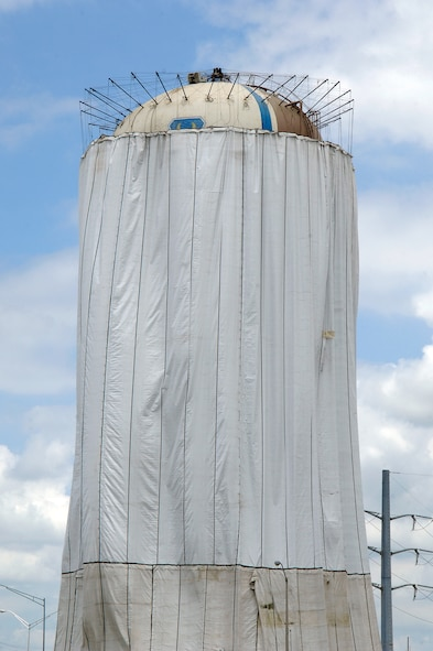 Tinker water towers that shadow I-40 near S.E. 29th street are being repainted.  The draping keeps the spraying paint on the tower and off passing cars and close buildings and protects the tower's finish during painting.  (Air Force photo by Margo Wright)