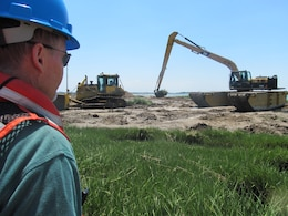 NEW YORK — Project Stakeholder from the New York State Department of Environmental Conservation watches hummock removal process on Yellow Bar Hassock marsh island.