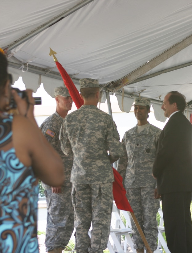 Brig. Gen. Michael Wehr (left) waits as outgoing Albuquerque District Commander Lt. Col. Jason Williams prepares to pass the command flag to incoming District Commander Lt. Col. Antoinette Gant during a ceremony July 12.  Also pictured (right) is the District's civilian Deputy for Planning, Projects and Program Management, John D'Antonio.