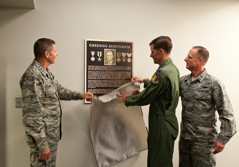 Lt. Gen. Robin Rand, 12th Air Force commander, Lt. Col. Christopher Clark, 432nd Attack Squadron commander, and Col. Mark Weatherington, 28th Bomb Wing commander, unveil a plaque dedicating the 432nd ATKS auditorium to Col. Ross Greening, a former member of the 432nd Bomb Squadron in the 1940s, at Ellsworth Air Force Base, S.D., July 12, 2012. The auditorium will be used for conducting aircrew briefings prior to combat support sorties, mass briefings for intelligence updates and aircrew/squadron personnel training vital to Ellsworth's MQ-9 operations. (U.S. Air Force photo by Airman 1st Class Alystria Maurer)